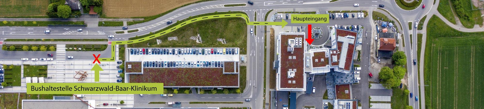 Steigen Sie an der Bushaltestelle Schwarzwald-Baar-Klinikum aus. Laufen Sie auf dem Gehweg vor dem Parkhaus bis zum Holiday Inn Gebäudekomplex.